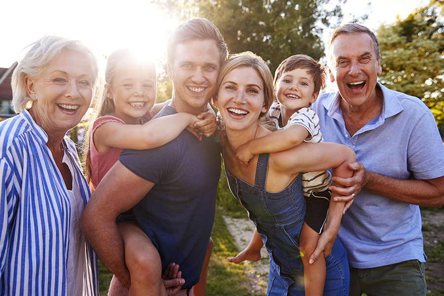 Personal Insurance - Portrait Of Happy Extended Family Standing Outside